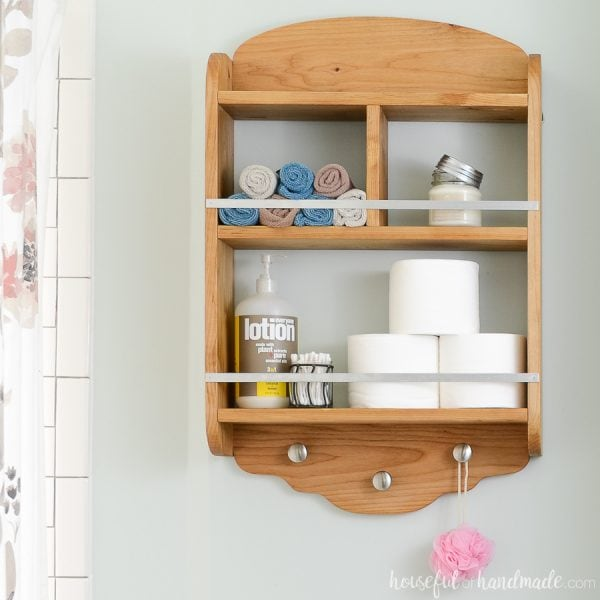 Wood bathroom storage shelves with metal details to hang over the toilet. Bathroom items like toilet paper and wash cloths stored on the farmhouse bathroom shelves.