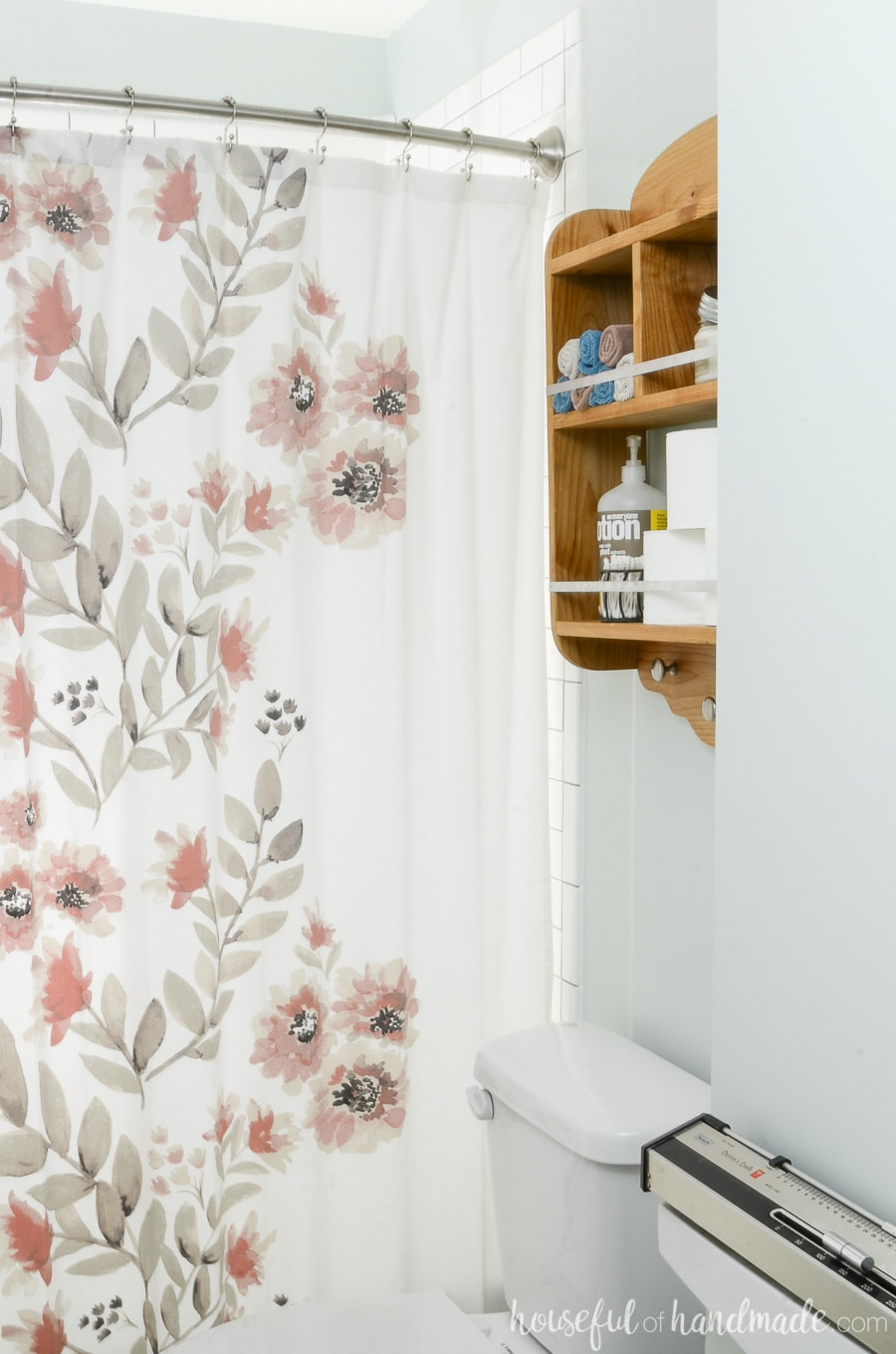 Wood over toilet shelves storing toilet paper and other bathroom items. Next to watercolor floral shower curtain.