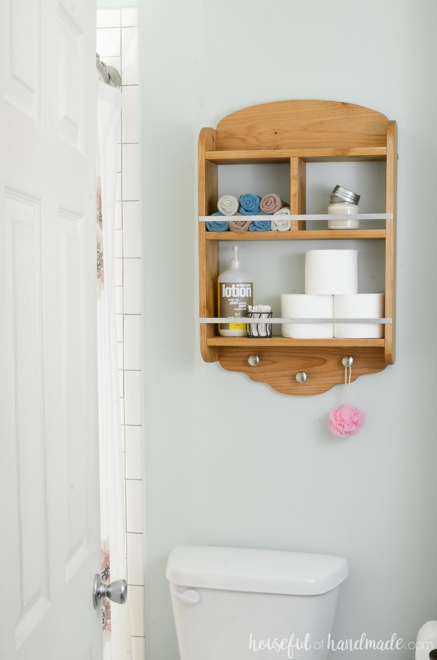 DIY bathroom storage shelves to hang above the toilet for extra storage. Wood shelves holding toilet paper, lotion and wash cloths.