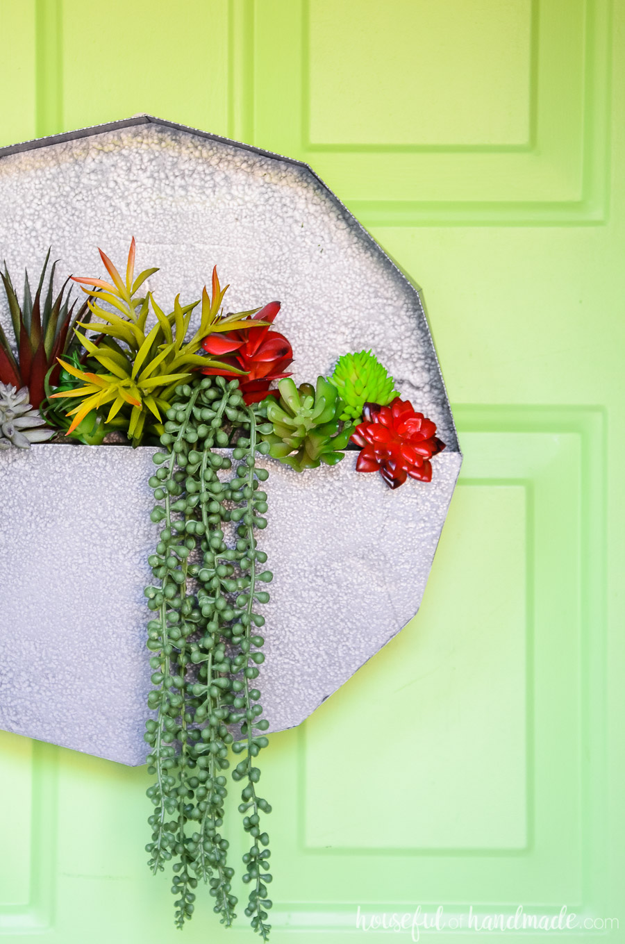 Easy succulent wall planter craft with red and green succulents inside and a faux metal paint.