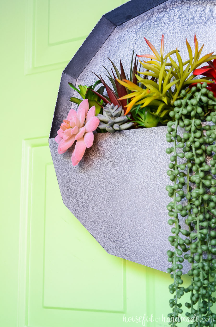 Faux metal succulent wall planter on a green door filled with fake succulents including string of pearl succulents hanging down.
