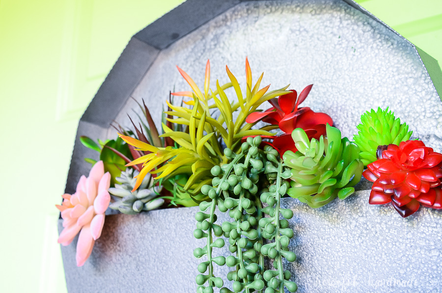 Close up of the faux succulents in the metal wall planter. Red, green, and pink succulents.