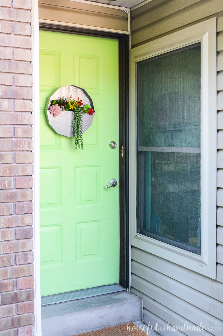 A succulent wall planter is a unique wreath door idea. Faux metal planter on a green door next to almond siding.