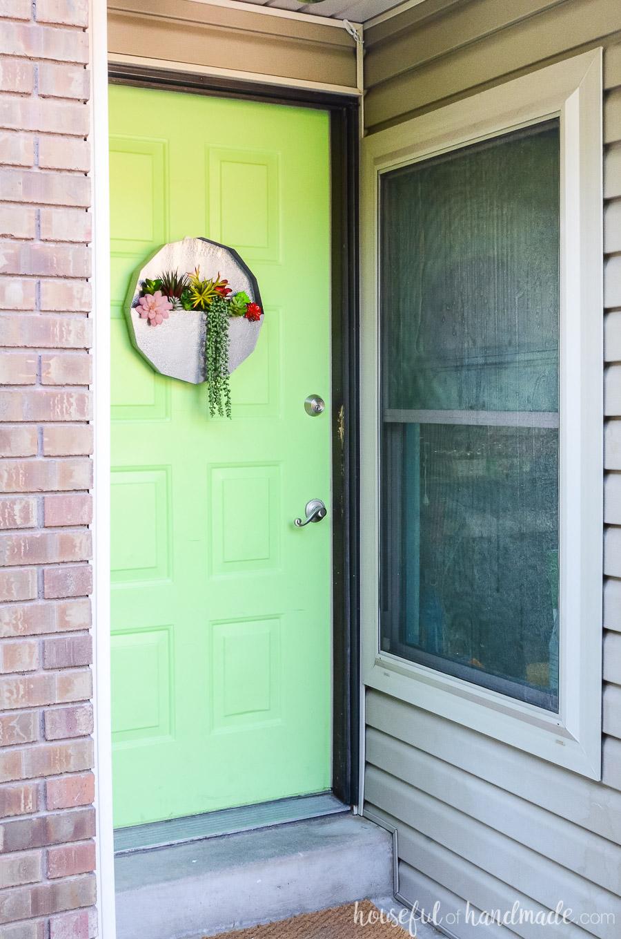 A succulent wall planter is a unique wreath door idea. Faux metal planter on a green door next to almond siding.
