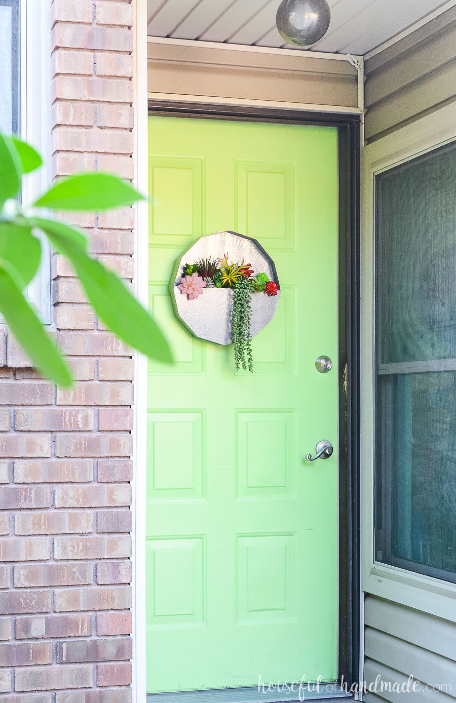 Bright green front door with metal succulent wall planter hanging on it as a wreath.