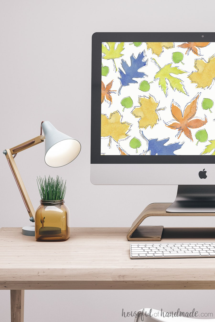 Computer on desk with lamp and plant showing free digital backgrounds on computer. Colorful autumn leaves digital wallpaper.