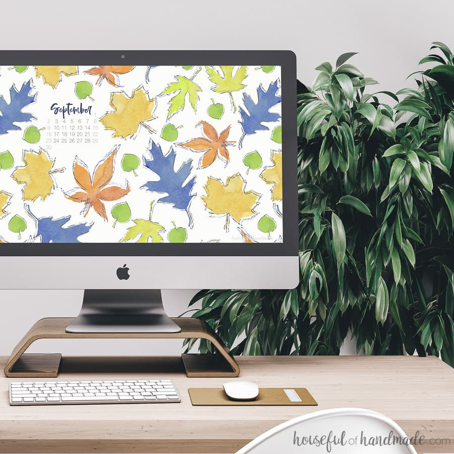 iMac computer on the desk with falling leaves digital wallpaper as the background. Free digital backgrounds for September at Housefulofhandmade.com.