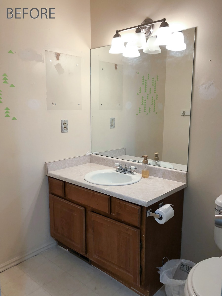 Old guest bathroom with oak builders grade vanity, large wall mirror and ugly off-white walls.
