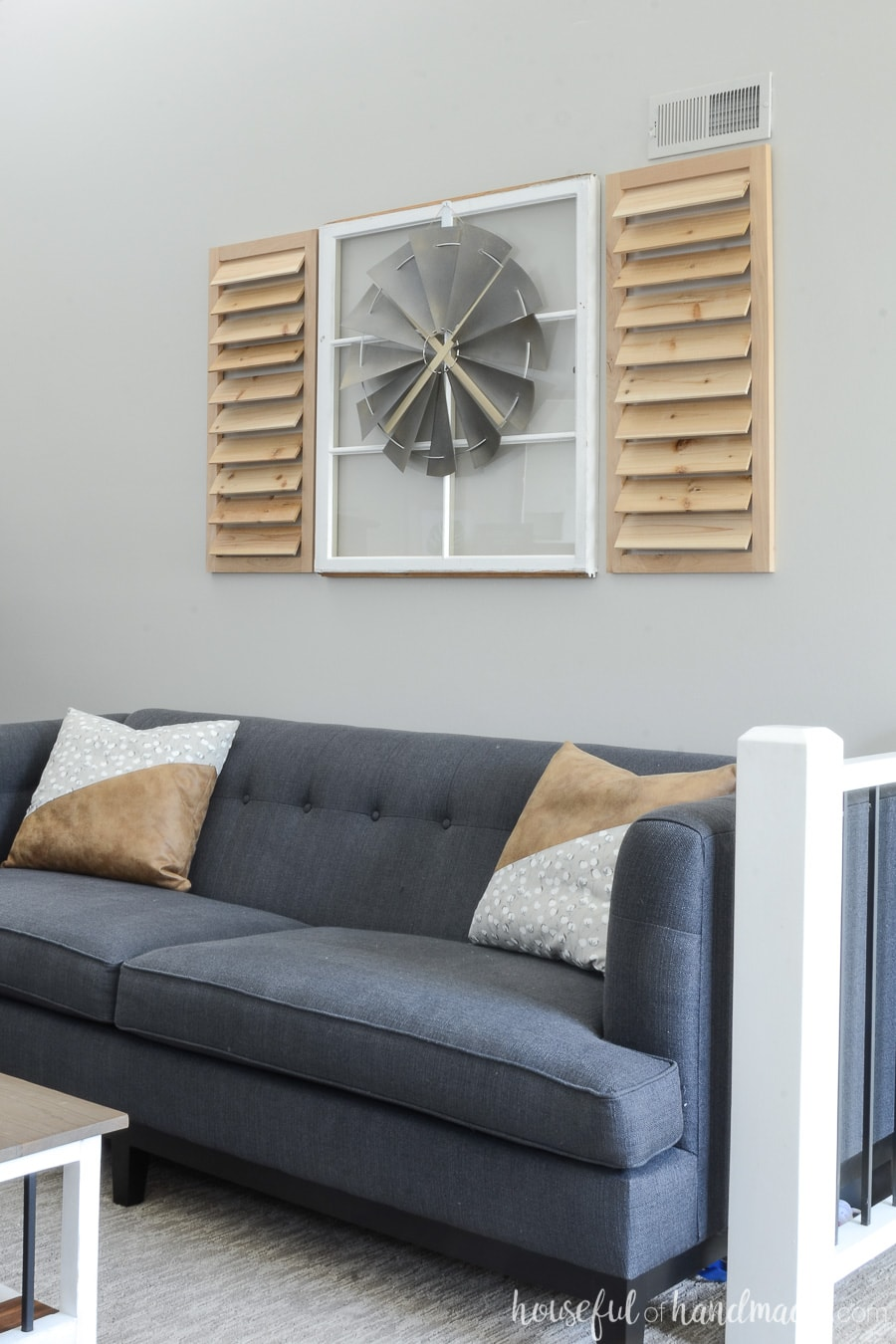 Old window and decorative windmill above a navy blue sofa.