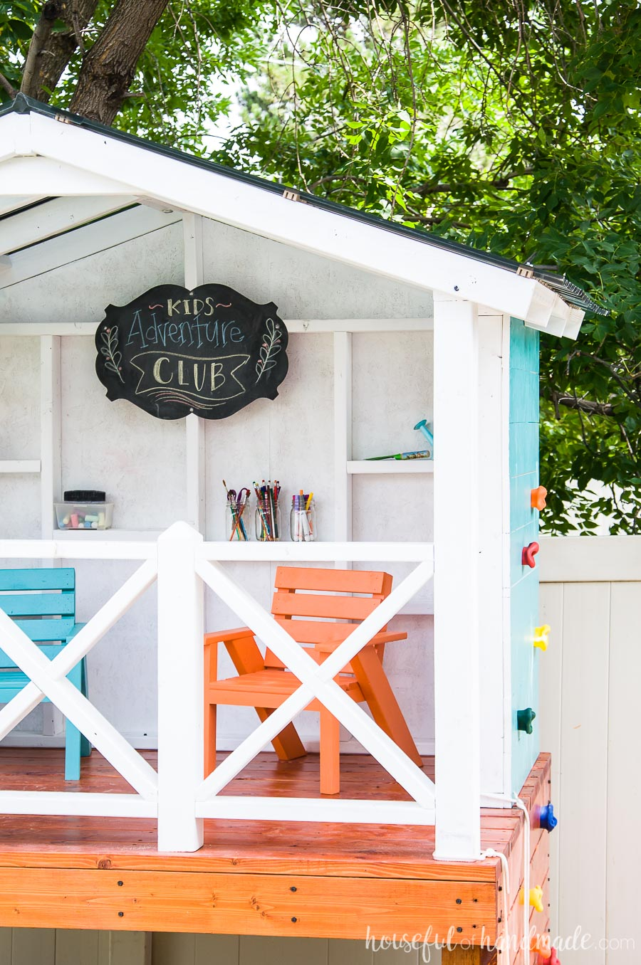 This kids playhouse is the perfect outdoor living space for any family. Orange and blue kids sized chairs inside.