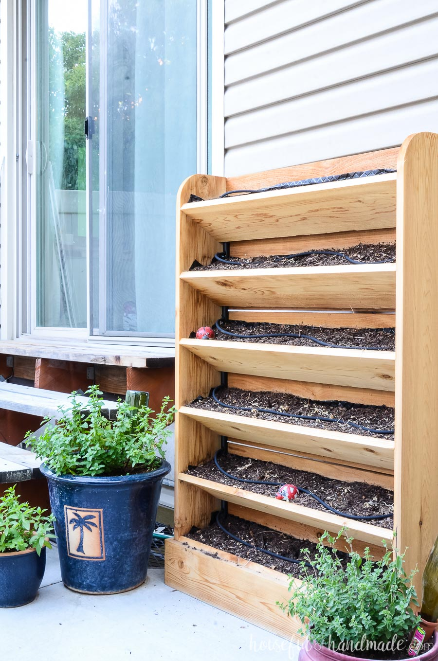Vertical cedar herb garden and potted herbs make a great accompaniment to an outdoor kitchen area.