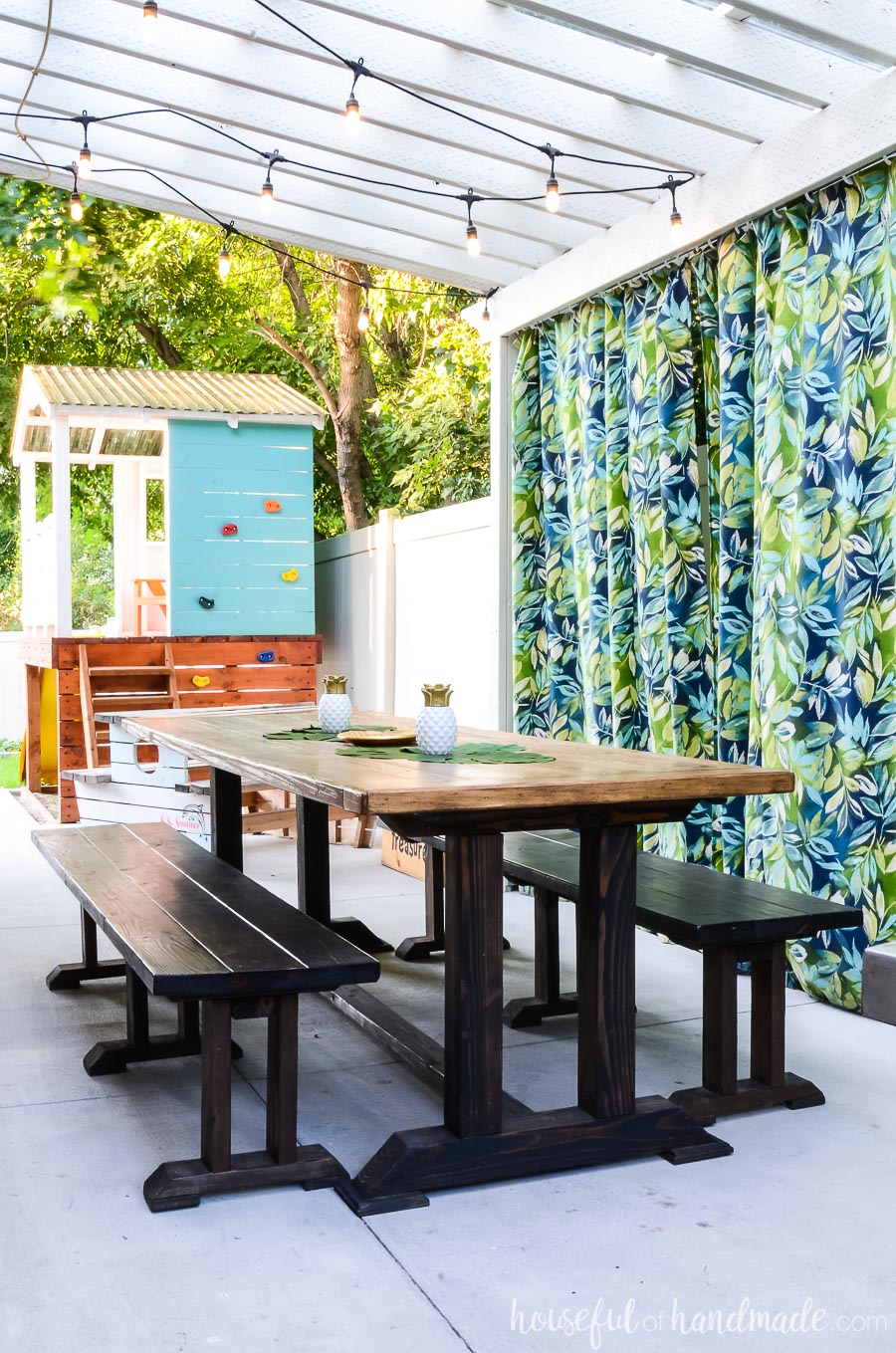 Island inspired outdoor living spaces. Patio pergola with tropical outdoor curtains and a large outdoor dining room. Kids play house in the background.