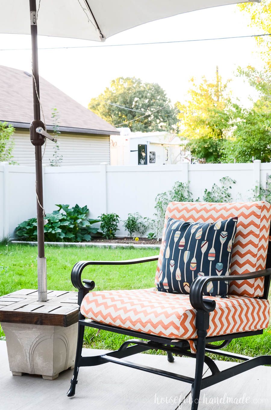 Handmade umbrella stand side table next to orange and white striped outdoor chair is one of our favorite outdoor living spaces.