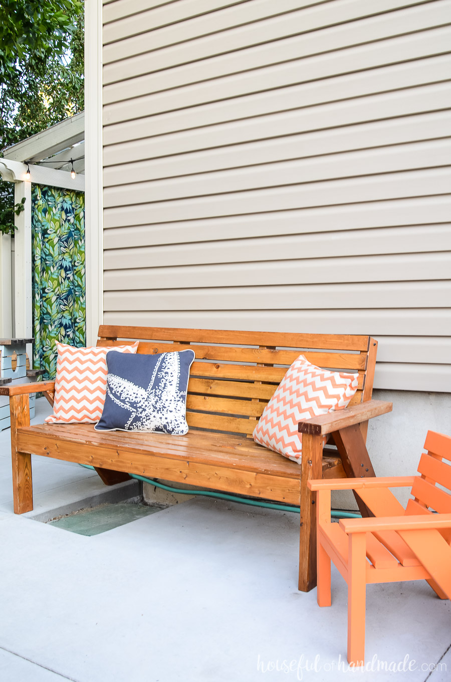 Slatted outdoor bench and kids chair with bright colored pillows make the perfect sitting area for one of our outdoor living spaces.