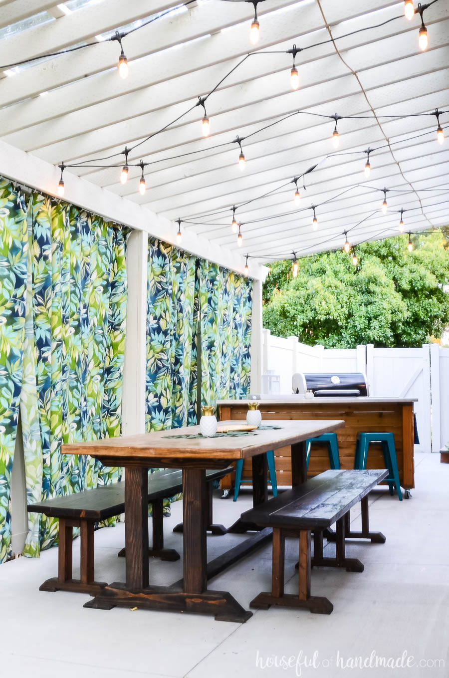 White pergola with lights over a large outdoor dining table with benches. Outdoor kitchen island next to the grill in the background.
