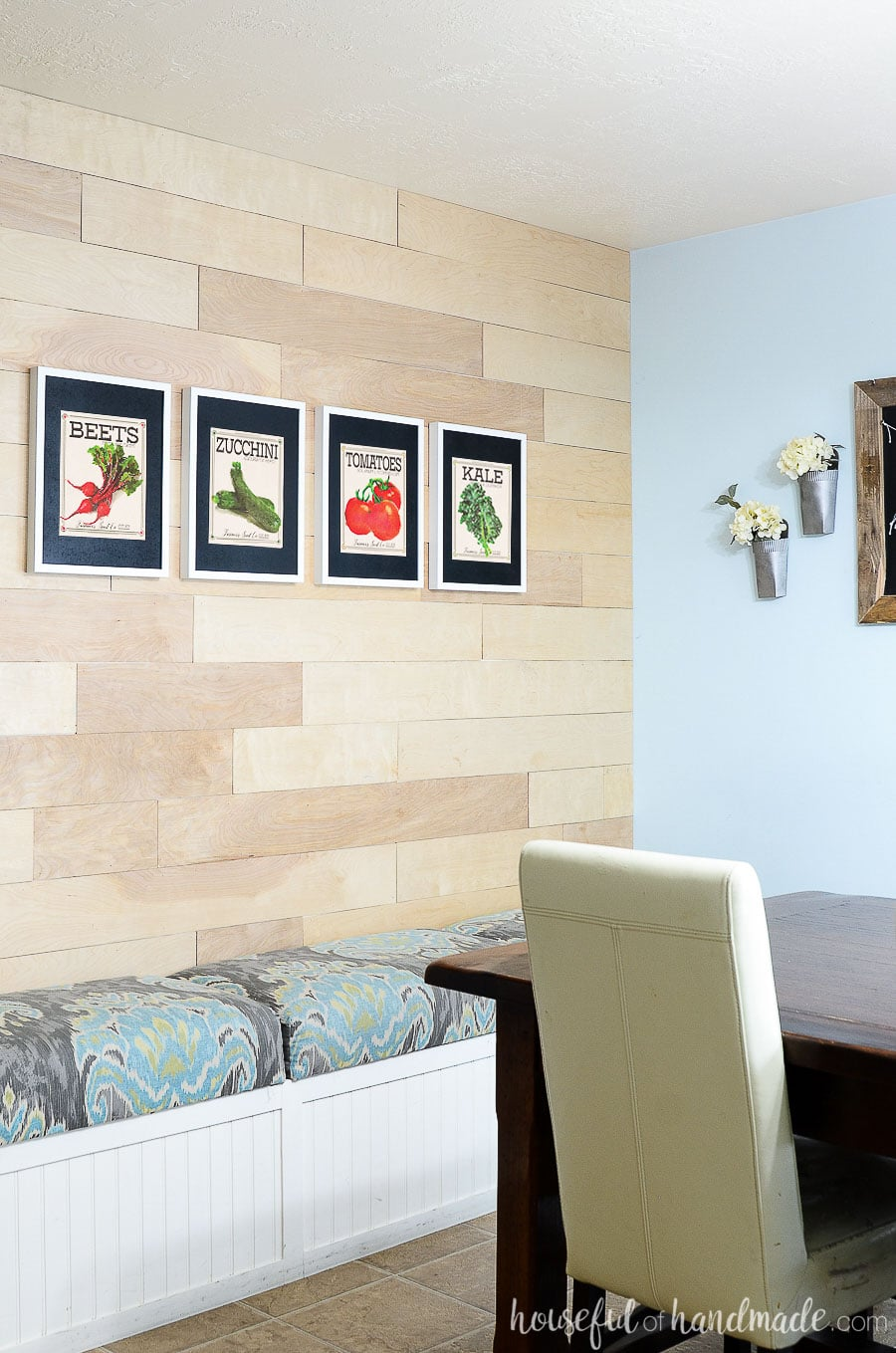 Vegetable seed packet art of beets, zucchini, tomatoes, and kale on the wood accent wall of the dining room.