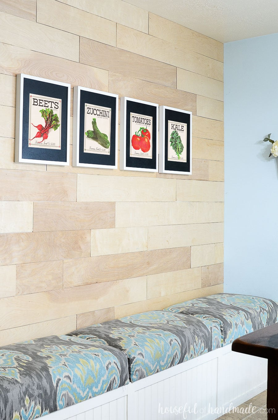 Wood wall with built in dining room bench and 4 vegetable seed packet art prints above it.