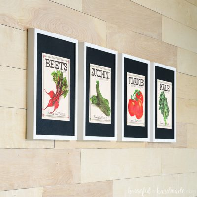 Four white picture frames with black mats highlighting vintage inspired vegetable seed packet art prints.