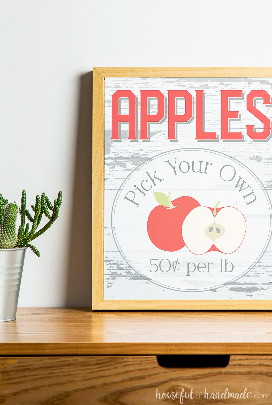 Apples Pick Your Own printable sign for fall decor in a frame on a table.