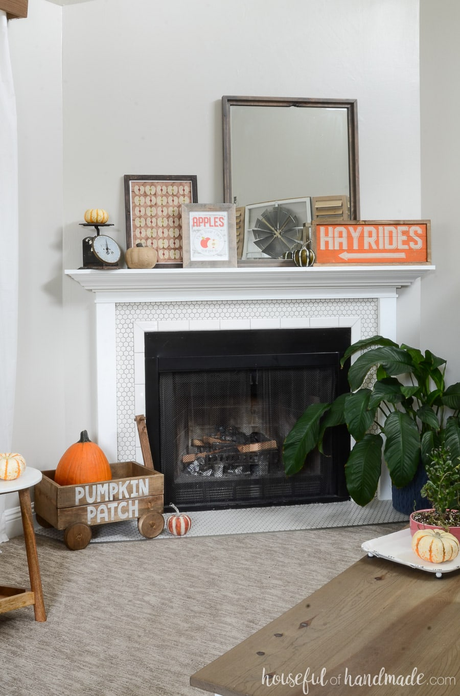 Decorate your mantel for fall with all your favorite fall traditions. This mantel has a wood hayrides sign, apple picking art, vintage scale, and pumpkins. A decorative wood wagon adds even more fall the hearth.