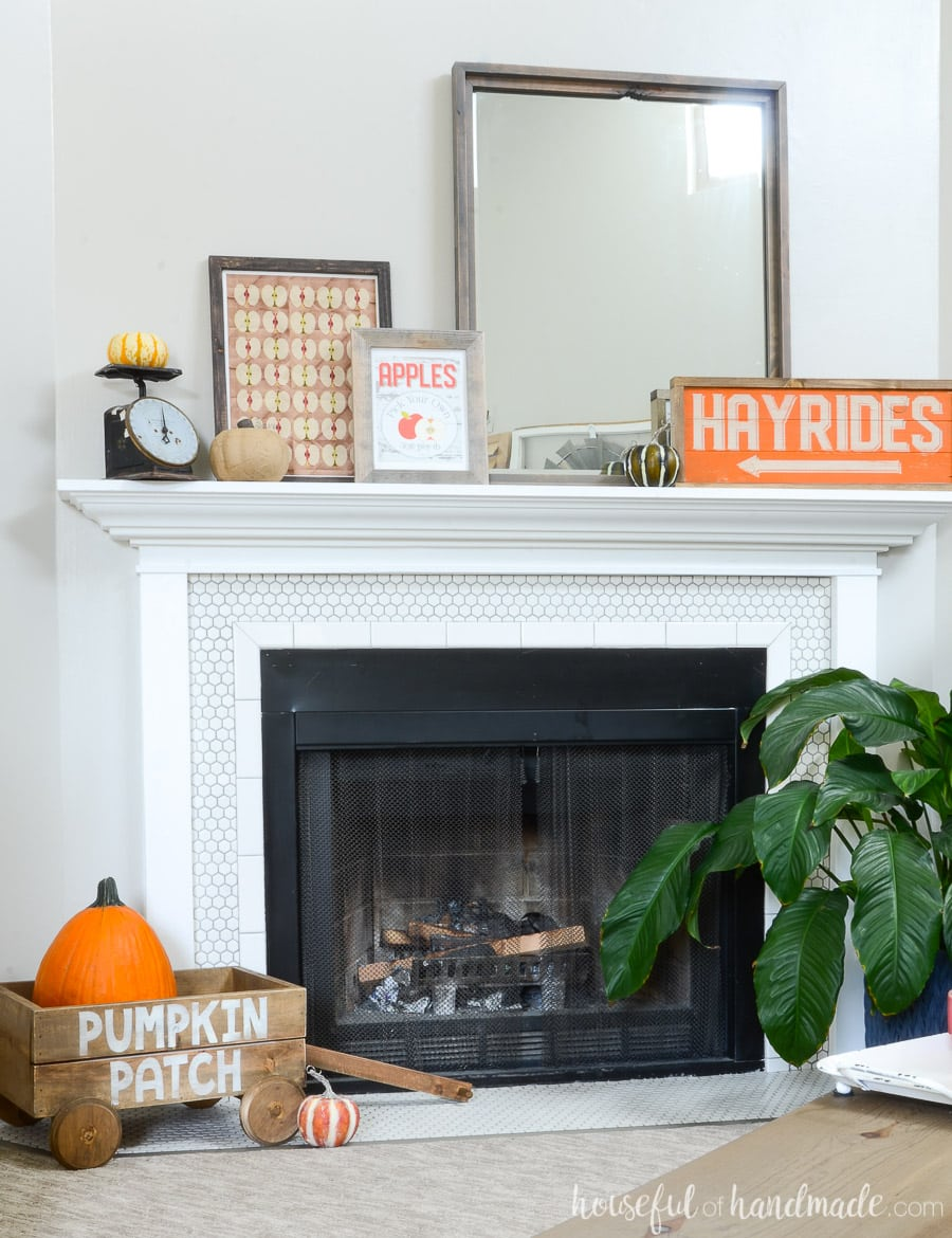 Beautiful white tiled fireplace with decor highlighting classic fall traditions: Orange Hayrides wood sign, apple picking printable signs, wooden pumpkin patch decorative wagon and lots of pumpkins.