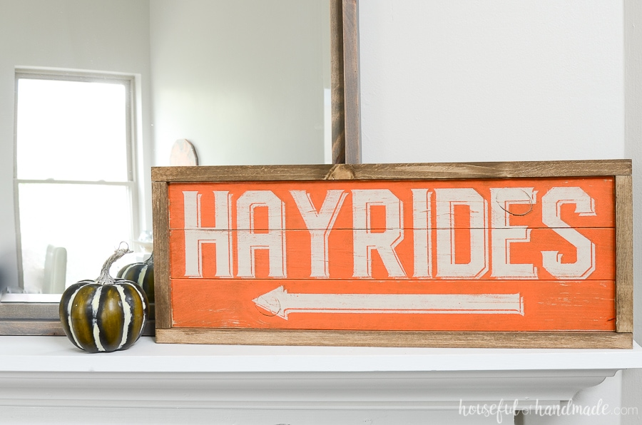 Orange and cream wood hayrides sign on the classic traditions fall mantel decor.