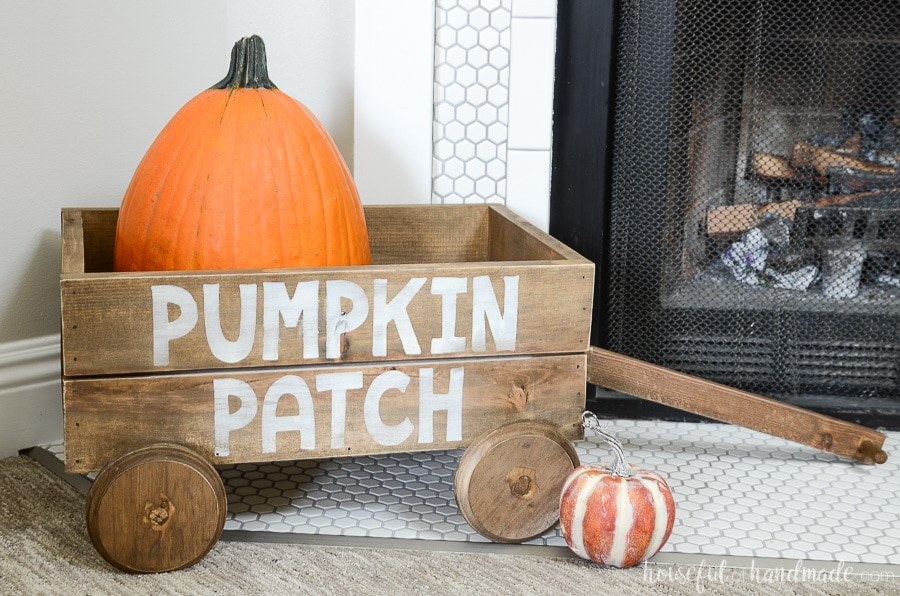 Decorative wooden wagon with large pumpkin in it. In front of the fall fireplace decor.