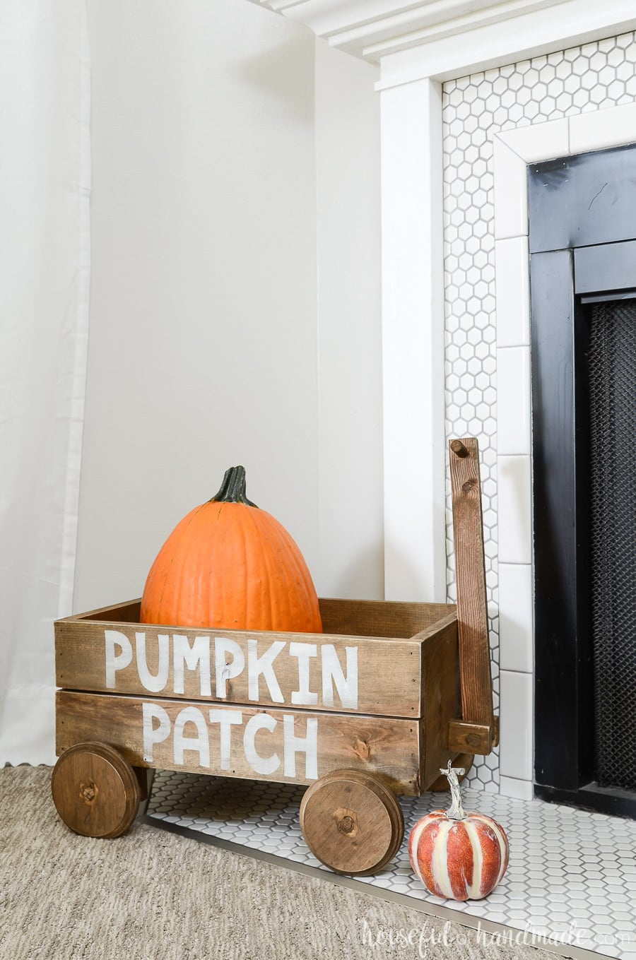 Aged wood wagon decor with pumpkin patch design on the side for fall fireplace decor.