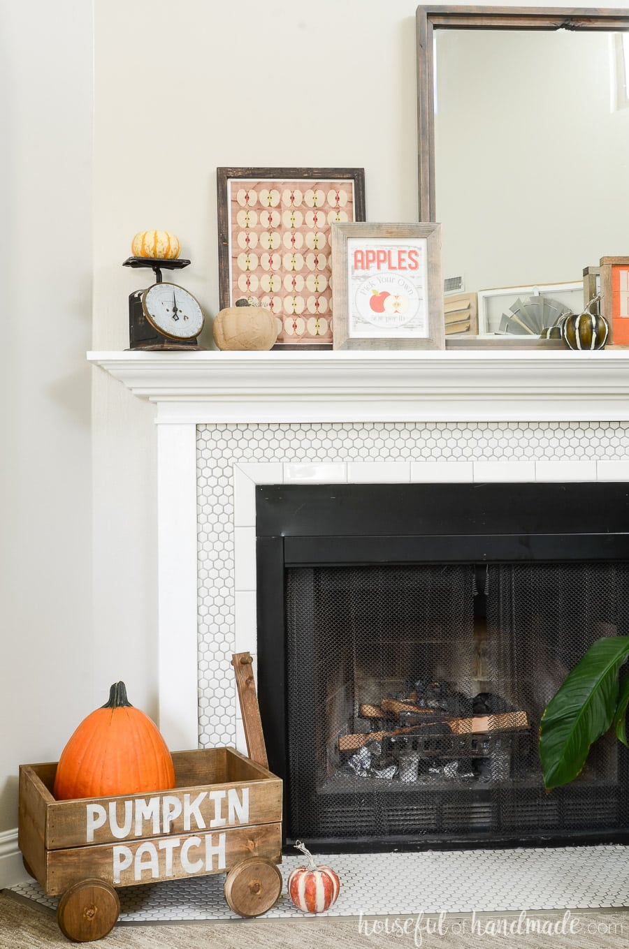 View of the entire fall mantel with the decorative wood wagon holding the pumpkin on the hearth.