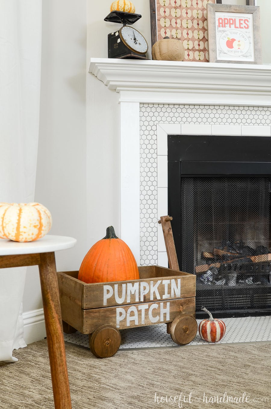 Decorative wood wagon with pumpkin patch words on the side holding a pumpkin on the fireplace hearth for fall decor.