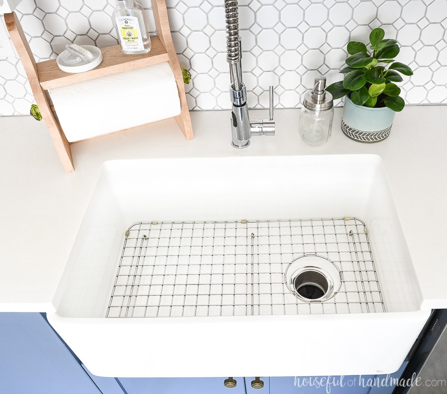 White fireclay farmhouse sink in a kitchen with white countertops and stainless steel sink grid in the bottom.