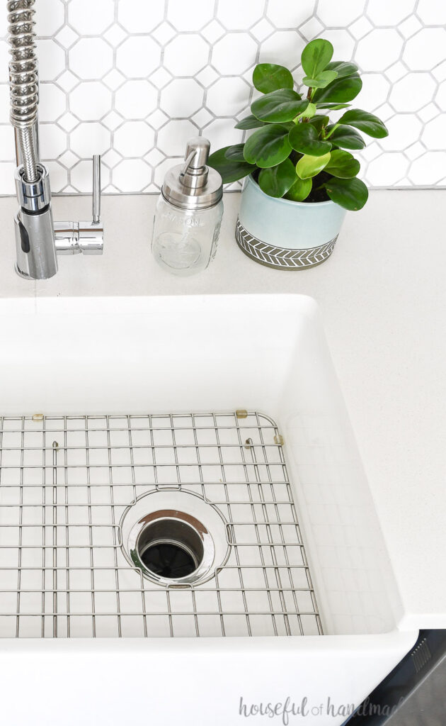 Beautiful farmhouse sink in a kitchen with white countertops and white and gray tile backsplash.