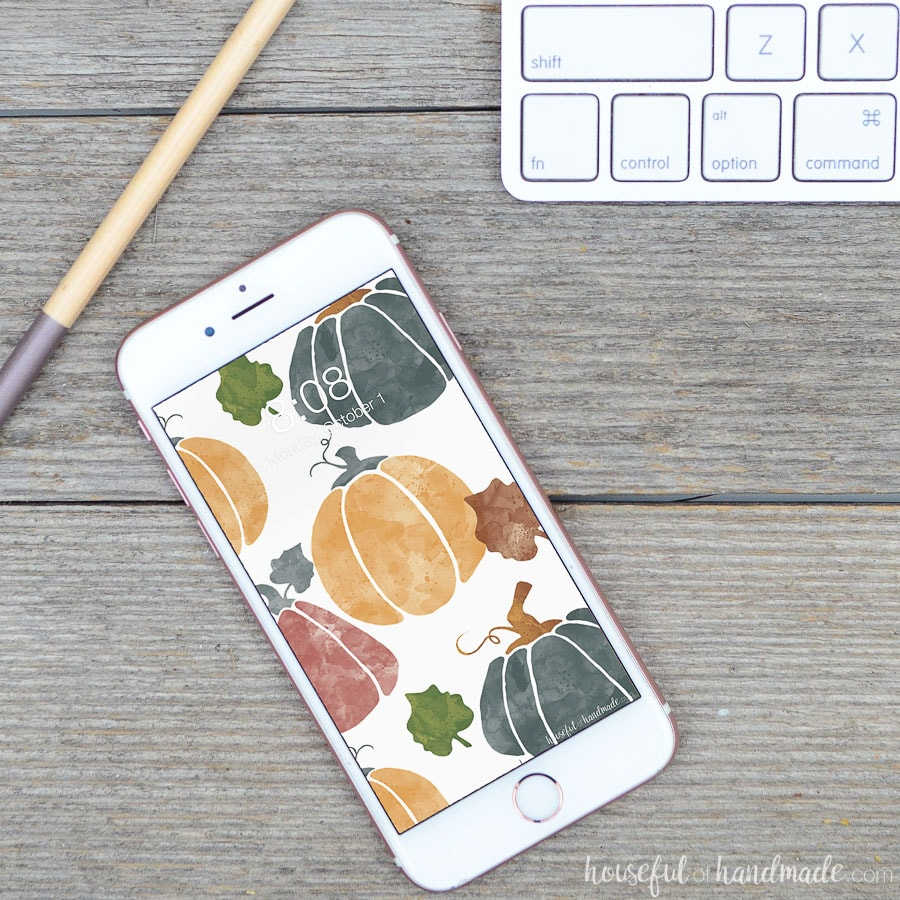 Watercolor pumpkin digital wallpaper on a white iPhone.