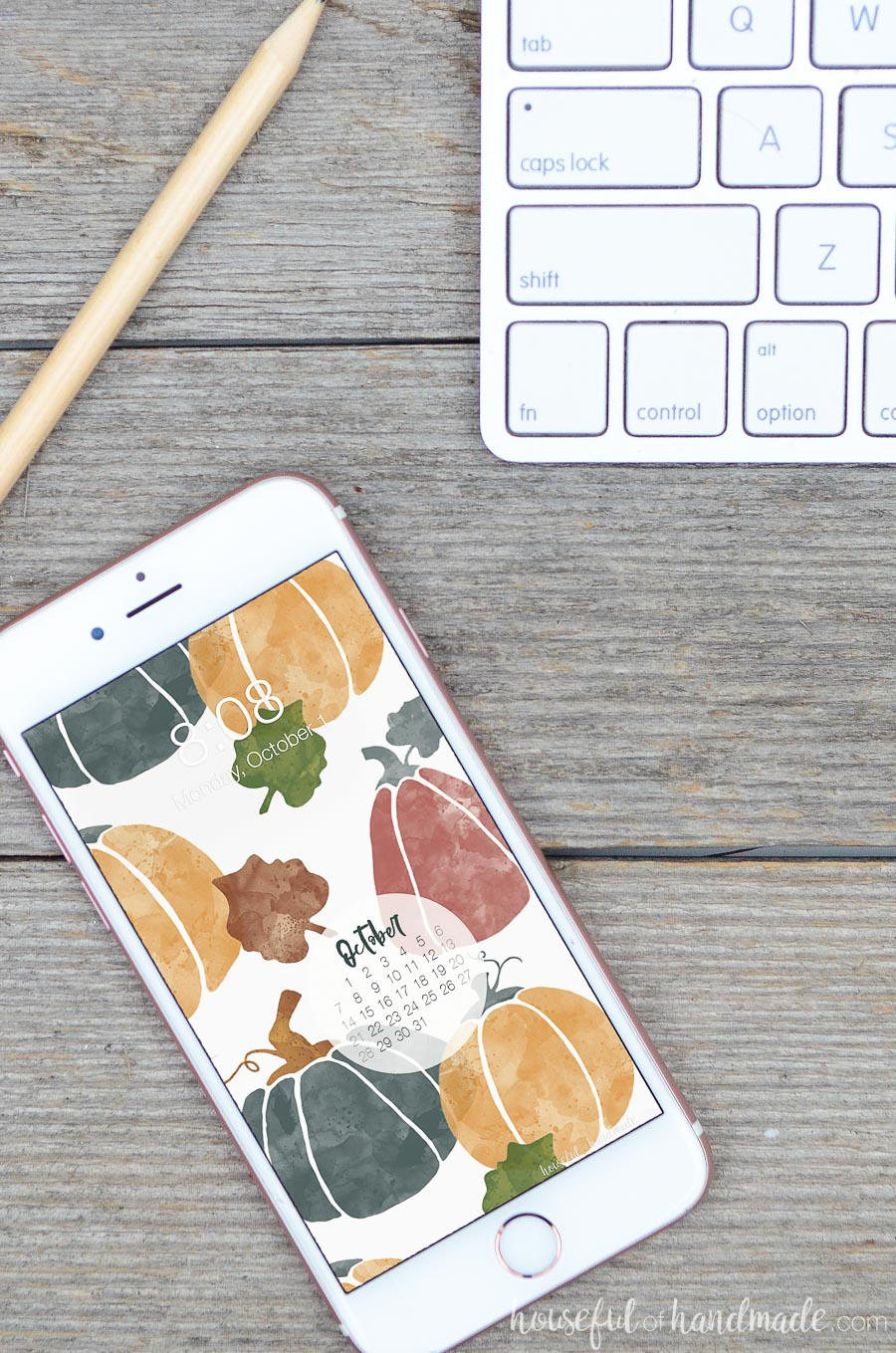 White smartphone with the pumpkin print free digital background for October on the lock screen.