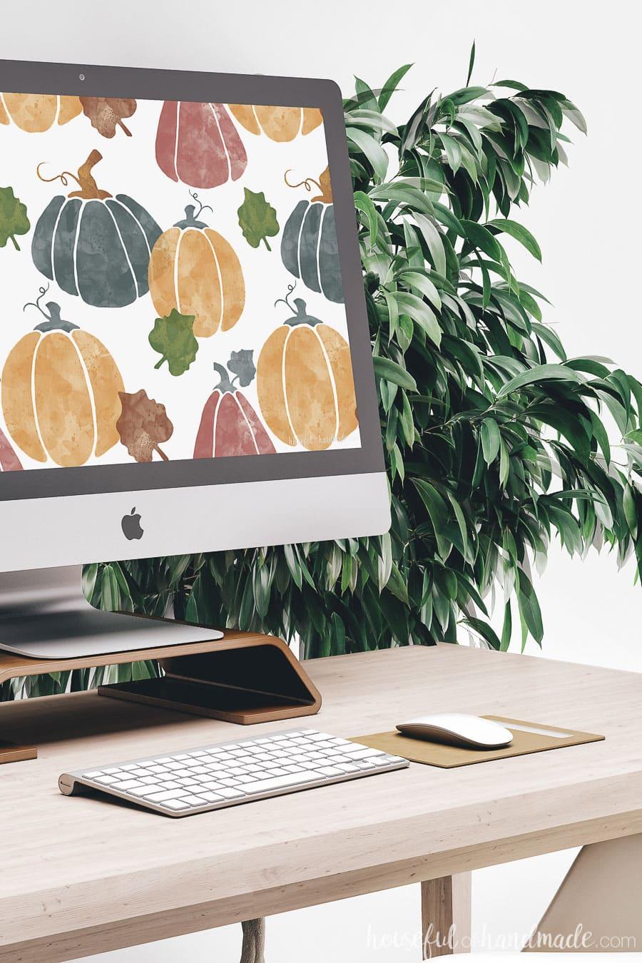 Desktop computer with watercolor pumpkin digital wallpaper design on the background.