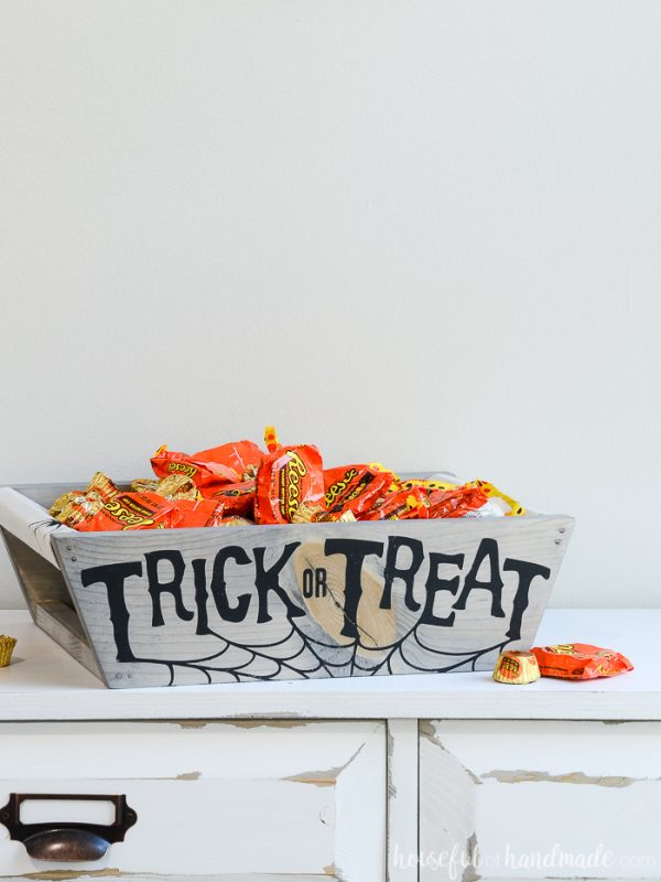 Wood Halloween treat basket with trick-or-treat spiderweb decor on the front of it.