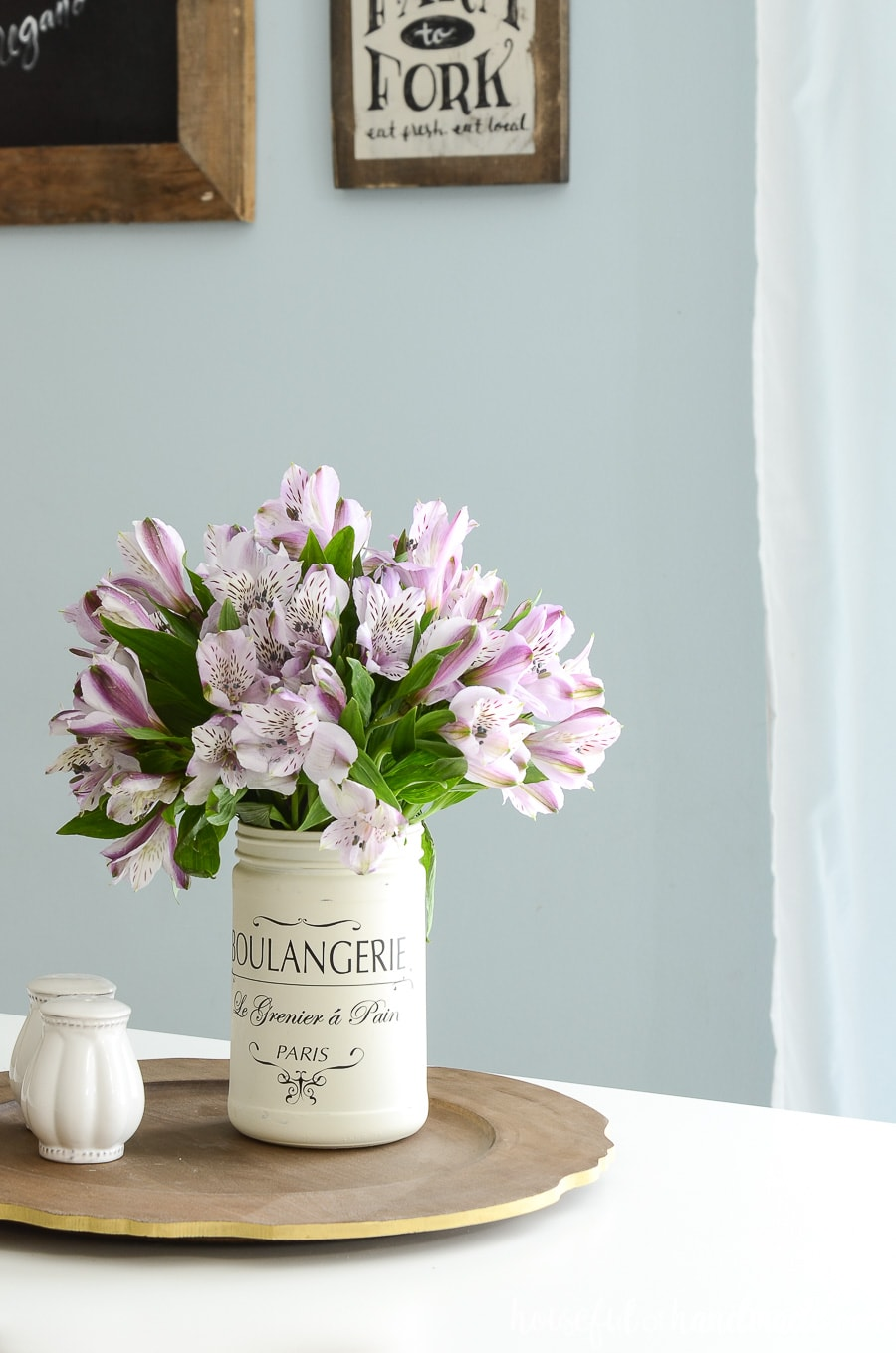 DIY farmhouse kitchen canister used as a vase with purple flowers sitting on an upcycled wood sign into a tray.