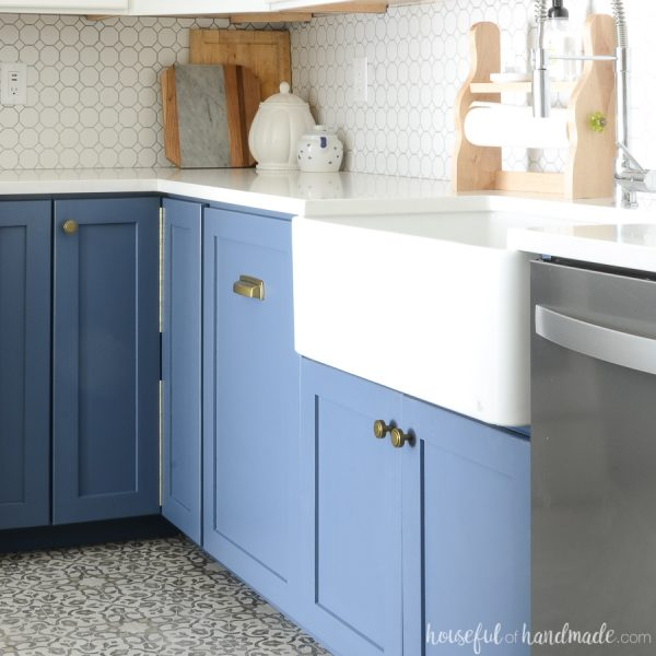 White farmhouse sink installed in a DIY farmhouse sink base cabinet painted blue.