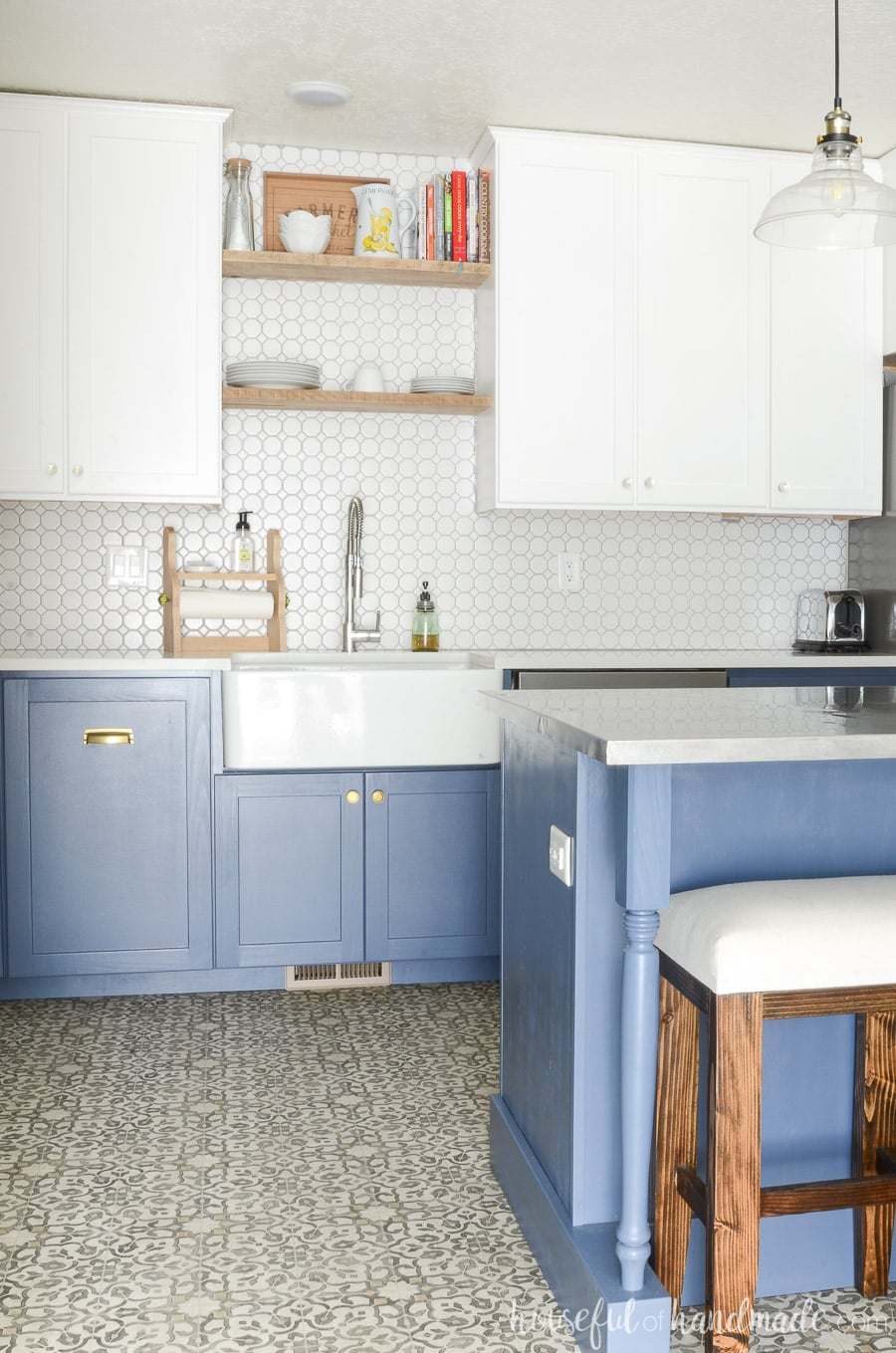 Beautiful farmhouse kitchen with blue & white cabinets and a large farmhouse kitchen sink.