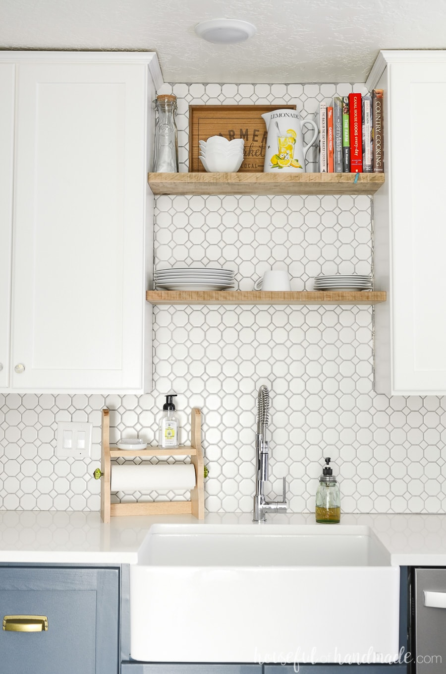 Large farmhouse sink in a kitchen with open shelving above the sink and white octagon tile backsplash.