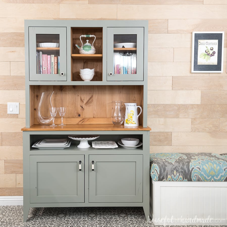 Gray hutch in the dining room against a wood feature wall.