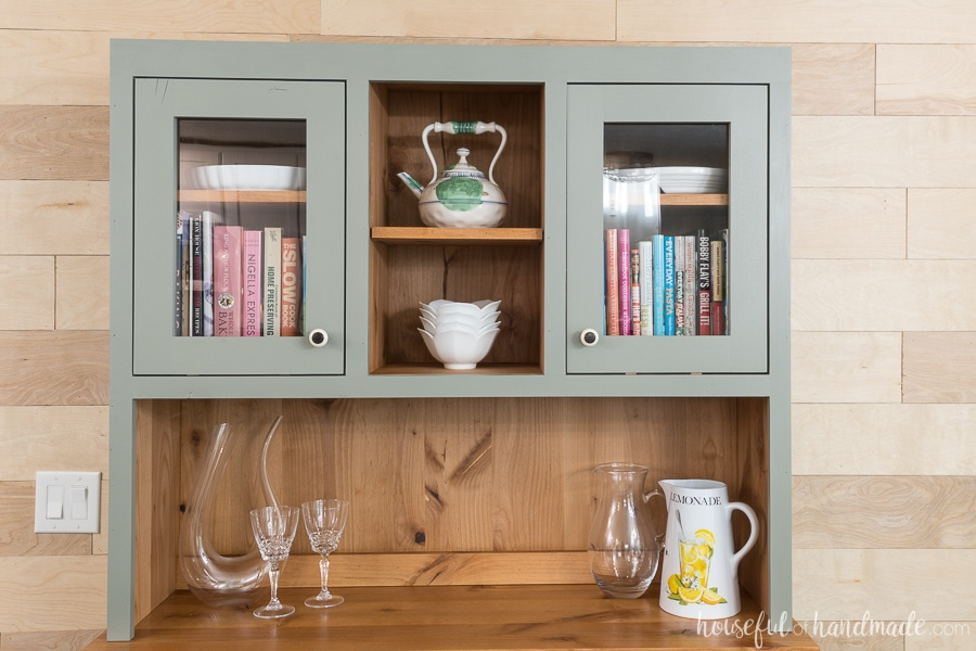 Natural wood hutch with painted gray interior storing platters, cook books, and baking dishes.