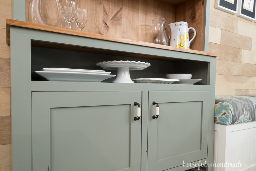 A narrow open shelf at the top of the dining room hutch is perfect for displaying and storing platters.