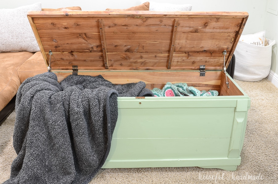 The refinished storage chest with the lid open showing all the blankets inside. One gray fluffy blanket draped out over the corner of the chest.