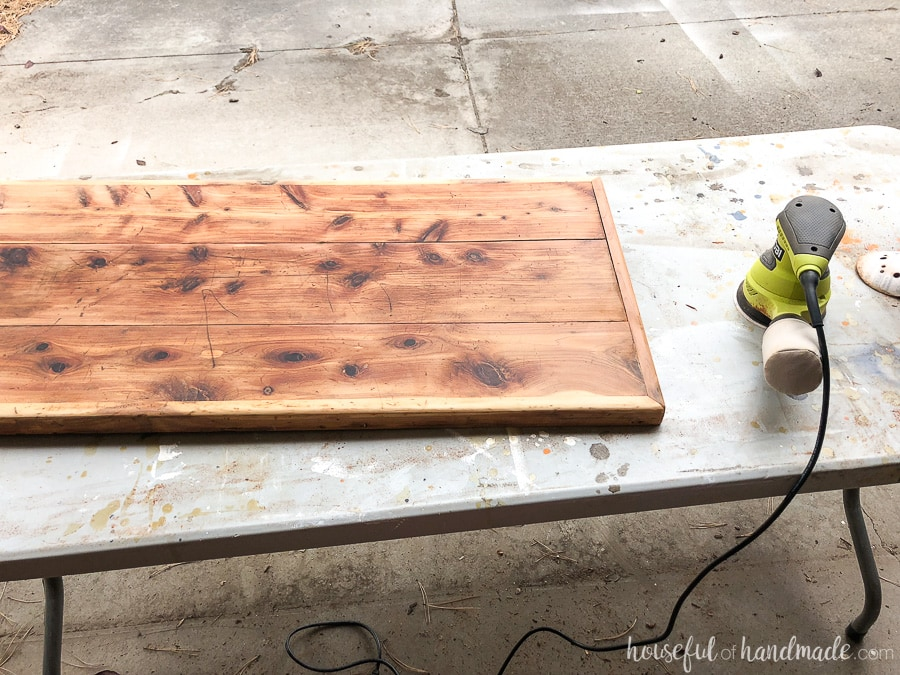 An orbital sander was used to remove the rest of the finish on the upcycled storage coffee table.