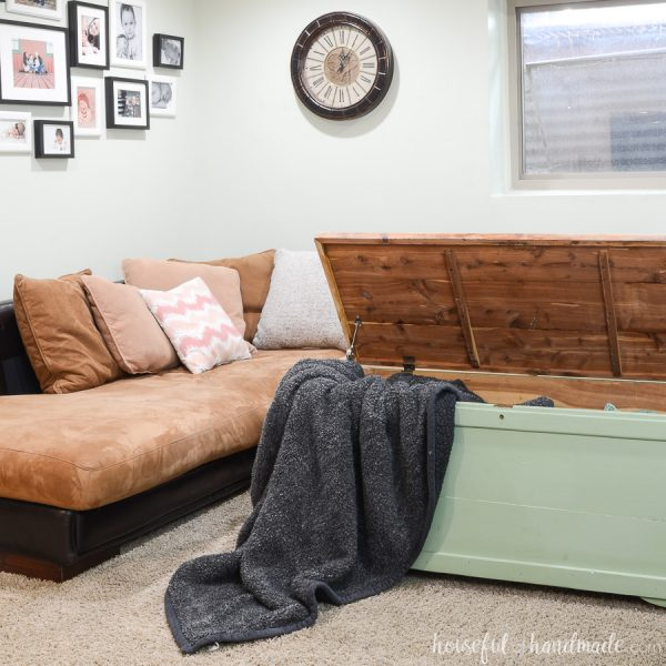 Green upcycled storage chest full of blankets being used as a coffee table.
