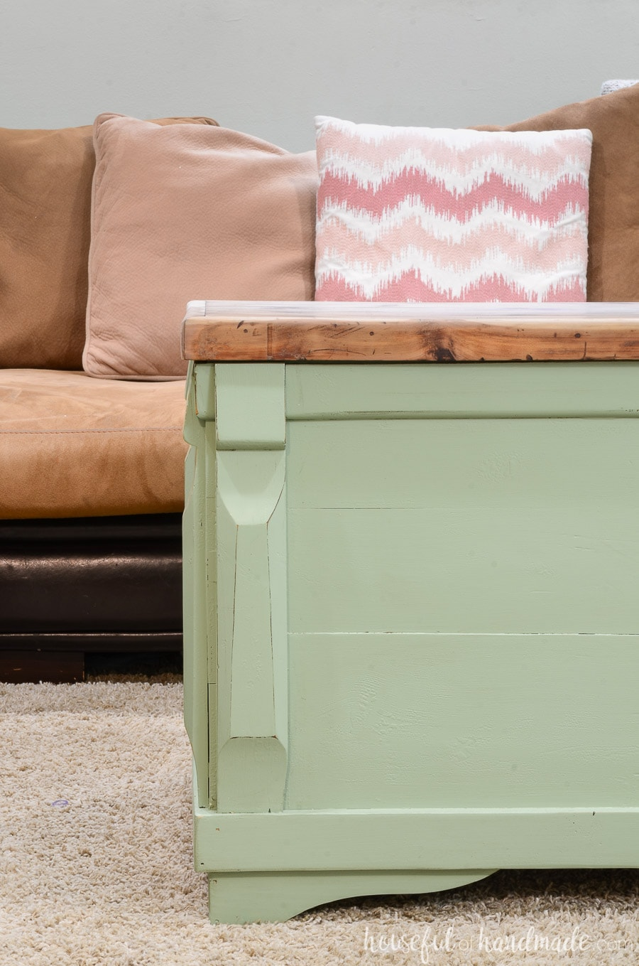 Close up of the refinished blanket chest being used as a coffee table. The base of the chest is painted green with slight distressing and the top is left wood toned.
