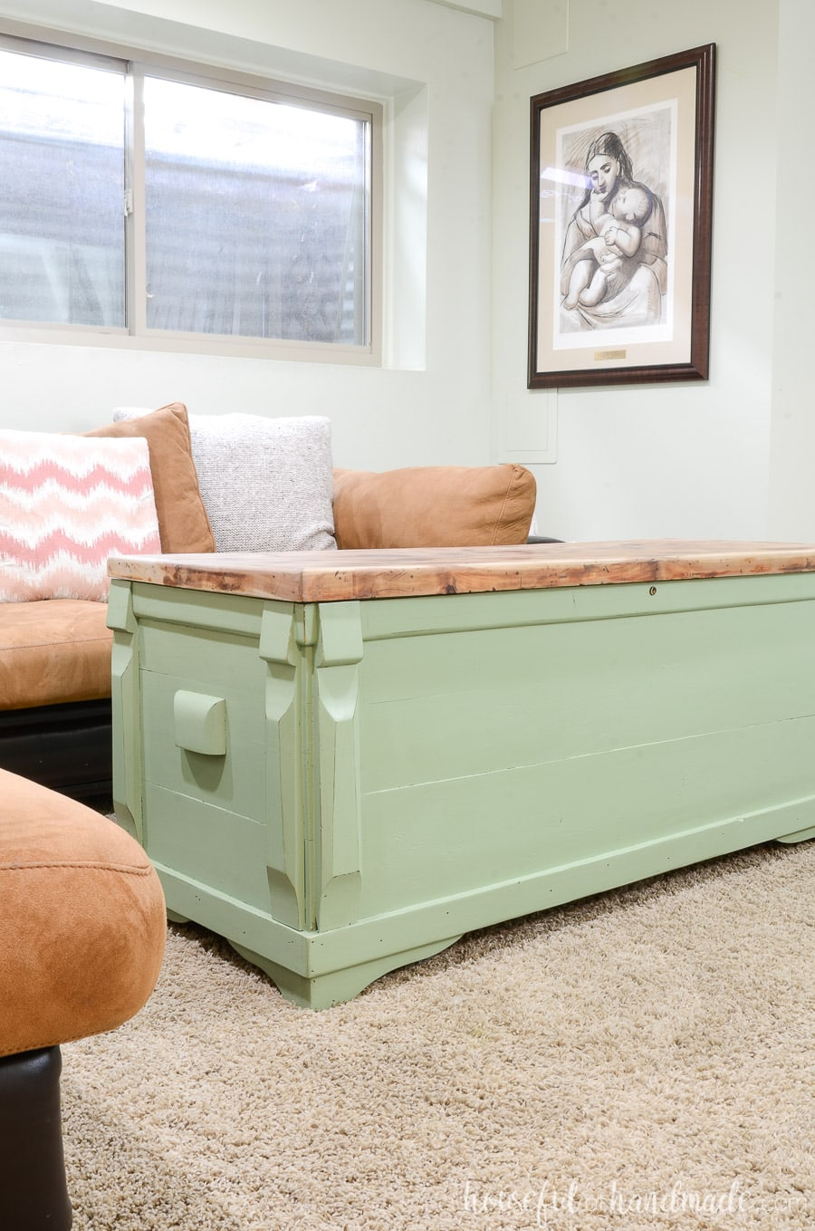 Living room with brown suede sectional and green painted storage chest used as a coffee table.