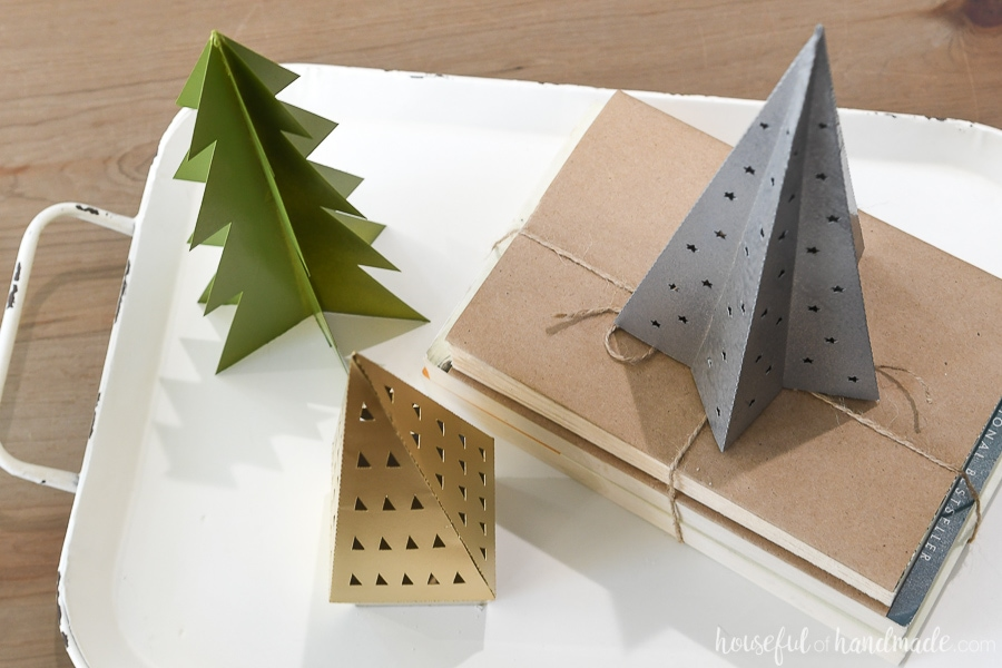 Overhead view of a vignette of paper Christmas trees on a tray.