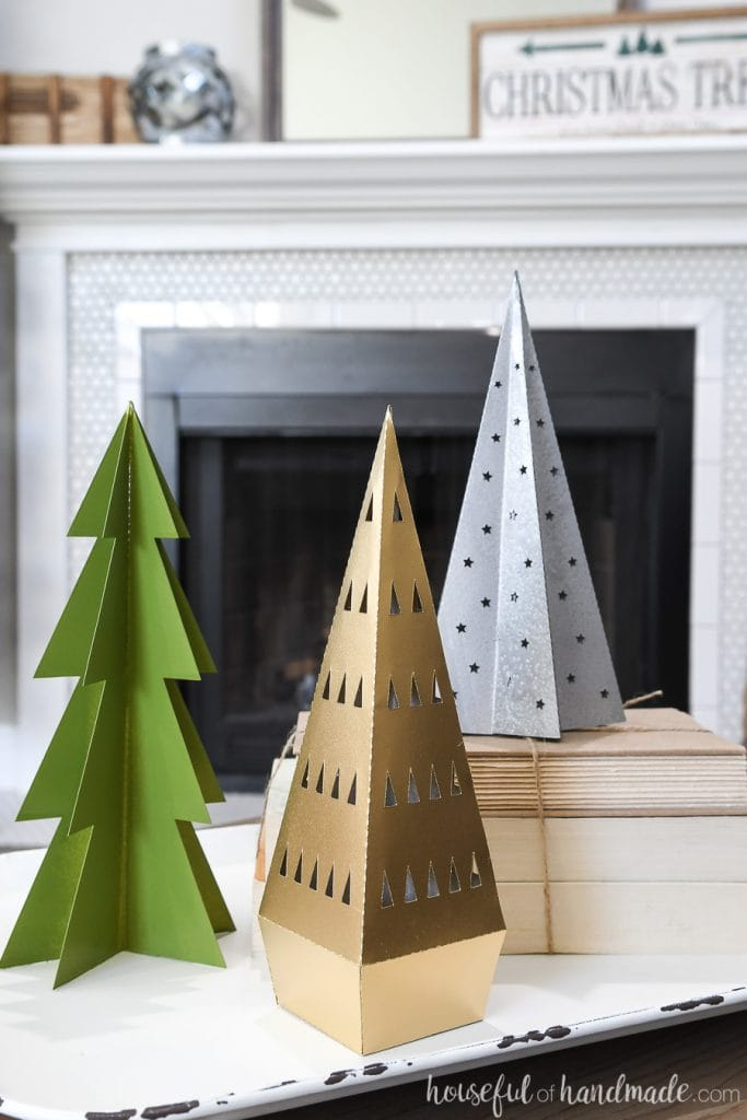 Gold, silver and green painted paper Christmas trees on a tray in front of the fireplace.